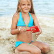 Little girl playing with sand on the beach — Stok fotoğraf
