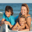 Happy woman and kids relaxing on a deck chair by the sea — Stock Photo