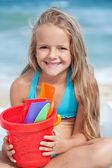 Niña en la playa con pequeña cubo y palas para arena — Foto de Stock
