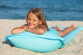 Little girl with inflatable mattress or raft on the beach — Stock Photo