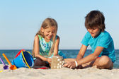 Kids playing on the beach building sand castle — Stock Photo