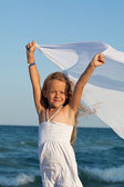 Little girl on sea shore playing with a kerchief in the wind — Stock Photo