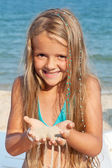 Little girl on the beach playing with sand — Stock Photo