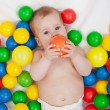 Chubby baby girl playing with colorful balls — Stock Photo