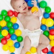 Happy baby boy with lots of colorful balls — Stock Photo