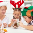 Happy family making a gingerbread cookie christmas tree — Stock Photo #32022671