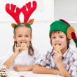 Kids with christmas hats eating gingerbread cookies — Stock Photo