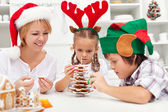 Happy family making a gingerbread cookie christmas tree — Stock Photo