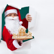 Santa giving you a gingerbread cookie house — Stock Photo