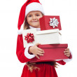 Little girl in santa costume holding presents — ストック写真