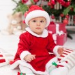Pretty baby girl in santa costume sitting — Stock Photo