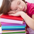 Exhausted young girl asleep on book stack — Stock Photo