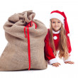 Little girl in christmas outfit hiding behind santa bag — Stock Photo