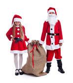 Santa und helfer mit einer großen tasche geschenke — Stockfoto