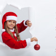 Little girl in santa costume leaning out of torn edges hole in p — Stock Photo