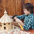 Boy building a bird house - mounting the last roof piece — Stock Photo