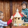 Kids painting the bird house for the winter — Stock Photo #36283463