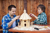 Father and son working on bird house together — Stock Photo