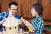 父亲和儿子建立一个鸟屋或进纸器 — 图库照片