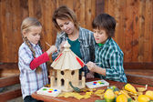 Woman with kids painting the bird house - preparing for winter — Stock Photo
