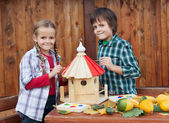 Kids painting the bird house - preparing for winter — Stock Photo