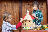 Kids painting the bird house for the winter — Stock Photo
