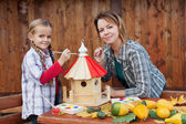 Woman and little girl painting a bird house — Stock Photo