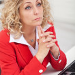 Business woman thinking at her desk — Stockfoto