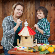 Woman and her son painting a bird house — Stock Photo