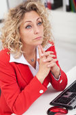 Business woman thinking at her desk — Stock Photo