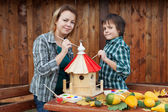 Woman and her son painting a bird house — Foto de Stock