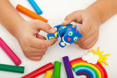 Child playing with colorful clay - closeup on hands — Stock Photo