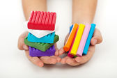 Child hands with colorful modeling clay — Stock Photo