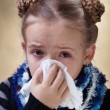 Little girl with the flu blowing her nose — Stock Photo #38804871