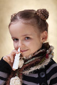 Little girl with nasal spray - fighting the flu — Stock Photo