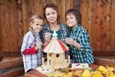 Family in autumn time preparing a bird house — Stock Photo