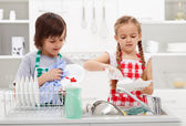 Kids washing the dishes in the kitchen — Stock Photo