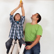 Boy helping his father to paint the room — Stock Photo #42002367