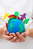 Modelling clay earth with rainbow and trees in child hands — Stock Photo