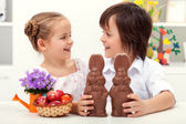 Happy kids at easter time with large chocolate bunnies — Stock Photo