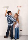 šťastný sourozenci malování pokoje v jejich novém domově — Stock fotografie