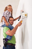 Happy father and little girl painting the room together — Stock Photo