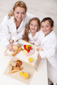 Woman and kids having a light and healthy snack — Stock Photo