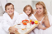 Woman having breakfast in bed with the kids — Stock Photo