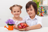 Kids dressed for celebration holding dyed easter eggs — Stockfoto