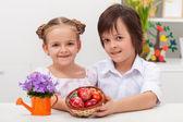 Kids dressed for celebration holding dyed easter eggs — Stock Photo