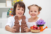 Happy kids with chocolate bunnies and other easter items — Stockfoto