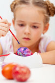 Little girl painting an artsy easter egg — Stock Photo