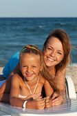 Happy woman and little girl at the sea side — Stock Photo