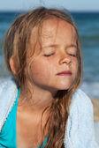 Liten flicka i solen på blåsiga havet — Stockfoto